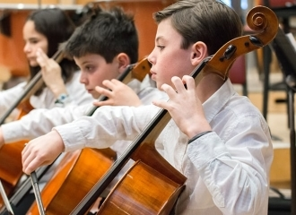 A group of boys playing the cello