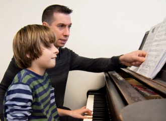 A man instructs a boy how to play the piano