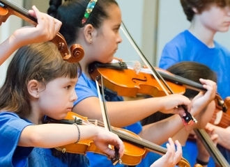 A group of young students rehearses the violin